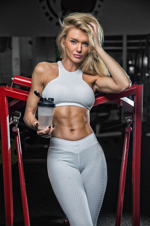 Beautiful blonde in a sporty shape drinks from a sheker sports nutrition