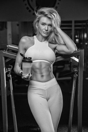 Beautiful blonde in a sporty shape drinks from a sheker sports nutrition