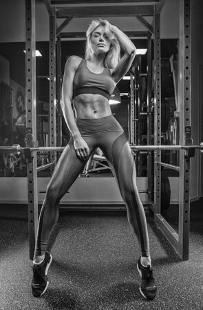 Beautiful blonde posing in front of the camera in the gym, wearing beautiful sportswear. Stock Photo