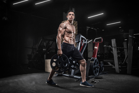 Handsome young man doing weightlifting exercises in the gym, squats, development of leg muscles. Stock Photo