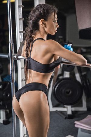fitness girl with shaker posing on bench in the gym Stockfoto