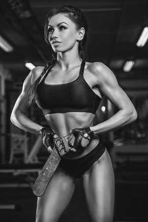 The girl in the gym crouches with a barbell, in a beautiful sports uniform, against a dark background.
