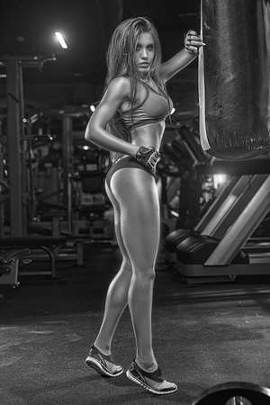 Beautiful fitness woman with lifting dumbbells . Sporty girl showing her well trained body .