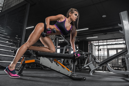 Fitness girl with dumbbells on a dark background
