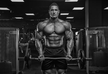 Bodybuilder-Gewichtheber des männlichen Athleten, in einem modernen Fitnessstudio, vor einem dunklen Hintergrund, der vor der Kamera aufwirft. Standard-Bild