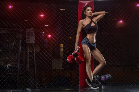 sporty woman with boxing gloves keeping arms raised while standing at gym Stockfoto
