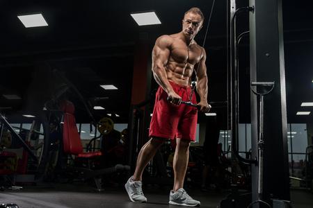 Muskulöser Mann, der im Fitnessstudio trainiert, Trizeps-Übungen macht, starker männlicher Oberkörperbauch Standard-Bild