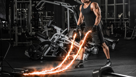 Men with battle rope battle ropes exercise in the fitness gym. CrossFit concept. gym, sport, rope, training, athlete, workout, exercises concept Фото со стока