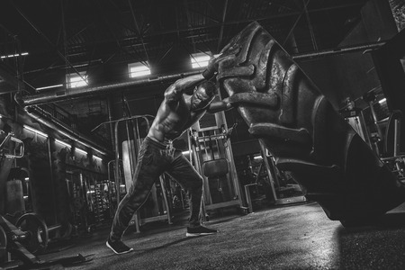 Muscular bearded tattooed fitness shirtless man moving large tire in street gym. Concept lifting, workout training Stock Photo