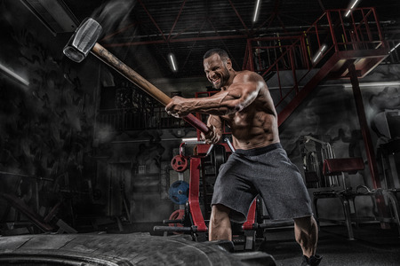 Man fitness training with large and heavy tire hits hammer. Concept workout, cross strength Stock Photo