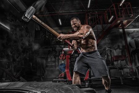 Trening fitness człowiek z dużymi i ciężkimi oponami uderza młotkiem. Trening koncepcyjny, siła krzyżowa