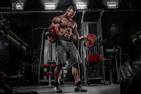 Power athletic guy standing with barbell, workout in the gym
