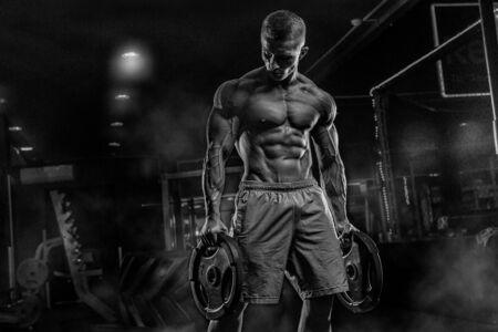 Male athlete bodybuilder posing on a black background Stock Photo