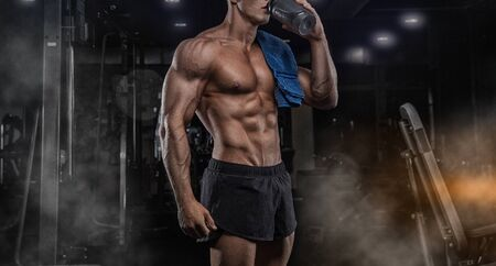 Handsome athletic fitness man holding a shaker and posing gym Standard-Bild