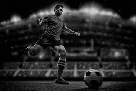 Soccer player in action on a dark background
