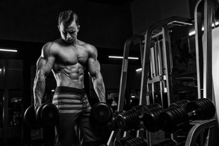 Muscular athletic bodybuilder man hard workout in gym over dark background with dramatic light with barbell Standard-Bild