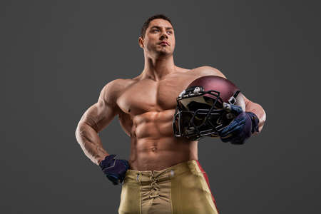 American football sportsman player on stadium with lights on background