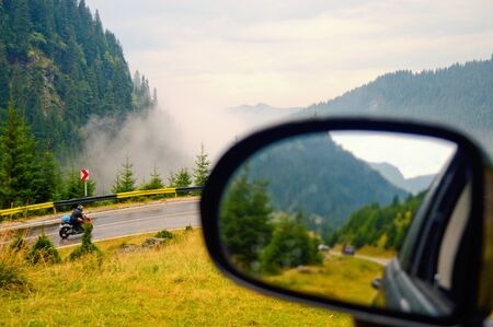 rear view mirror with a soft blurry reflection of a mountain road against backdrop of the blue cloudy sky Imagens