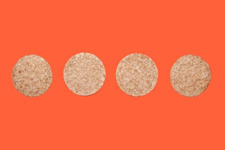 four rice or corn biscuits on an orange-carrot color background, top view of crispy cookies for food design and healthy eating, copy space