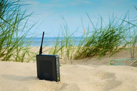 router on the sand on a summer day, the concept of modern technology, remote work, a network for freelancers