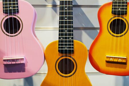 pink, brown and yellow ukulele guitar in the shop on the background of the wall