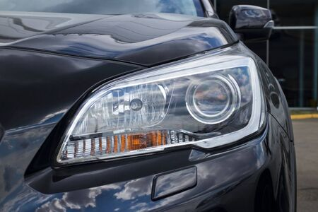 headlight of a black car, concept of the automobile market and the automotive industry, driving lessons and obtaining a driver's license 版權商用圖片