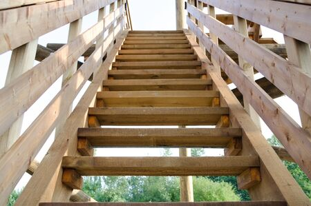 new wooden staircase outdoors in summer day, symbolizing career advancement and life changes