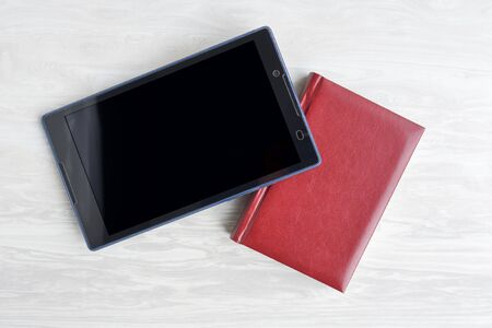 classic paper notepad and modern tablet, old and new way of recording addresses, phone numbers and storing information Stock Photo