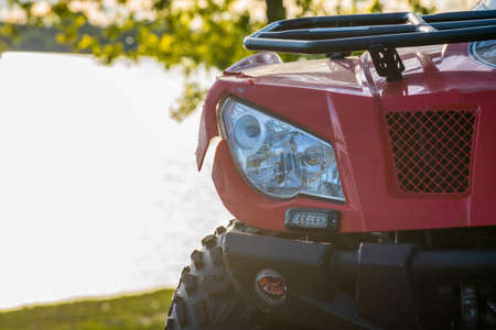 close-up front view of red atv quad bike, off road adventures, tours and traveling on all terrain vehicle in countryside