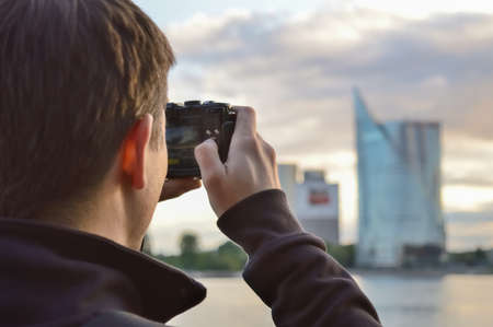 camera in the hands of a young journalist photographing a cityscape, selective focus and blurry background