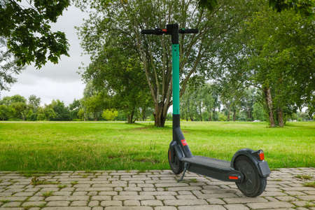 Electric scooter parked for hire on nature background, everyday transport for eco-friendly smart cities, ready for rent and online booking on app Reklamní fotografie