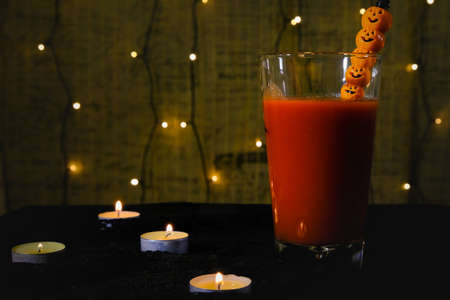 lit candles and blood filled glass with jack o'lantern style straw, mysterious atmosphere, composition and Halloween themed decoration 免版税图像
