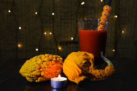 decorative pumpkins with lit candle in front and blood filled glass with jack o'lantern style straw, mysterious atmosphere of witchcraft and vampires on scary Halloween night