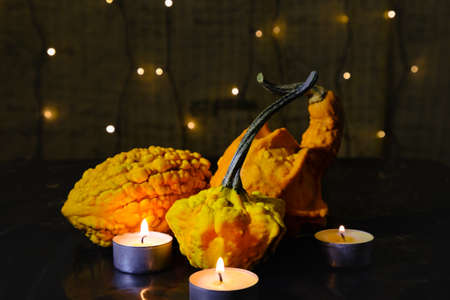 various decorative pumpkins and burning candles on background of blurry garland lights, dark mysterious atmosphere and home decoration for a scary Halloween night