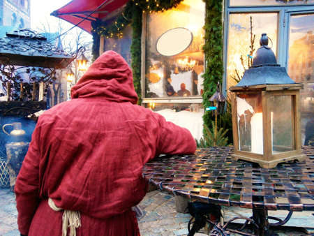 back view of the figure of a catholic monk in a red medieval robe on the town square at the christmas market and new year holidays