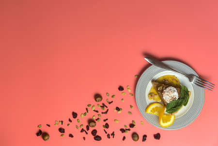 Piece of delicious pumpkin pie with fresh mint leaves, cream, cinnamon, maple syrup and slice of orange on white dish with fork on pink background. Happy Thanksgiving. Dublin, Ireland