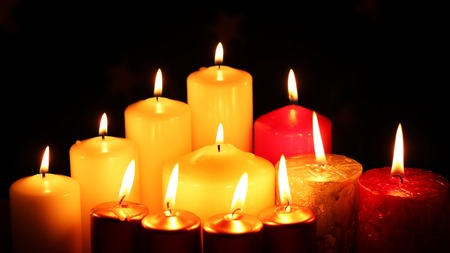 holy night: Many different multicolored candles lit in darkness out of focus and blur. Candle burn fire. Romantic or RIP template