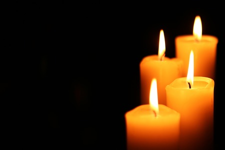 four big different burning candles bright light on dark background