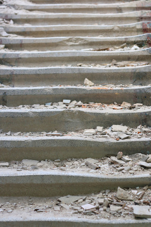 Old destroyed stairs rising upwards. The debris is on the stairs.
