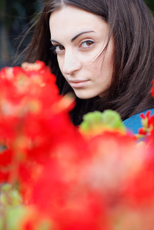 young girl portrait , windy hair, red flowers on the front line photo