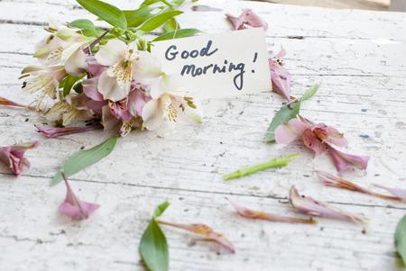 spread around: Pink Astromeria flowers in a white jar vase with good morning note spread around Stock Photo