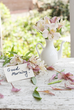 Pink astromeria flowers in a white jar vase with good morning pink astromeria flowers in a white jar vase with good morning note spread around stock photo mightylinksfo
