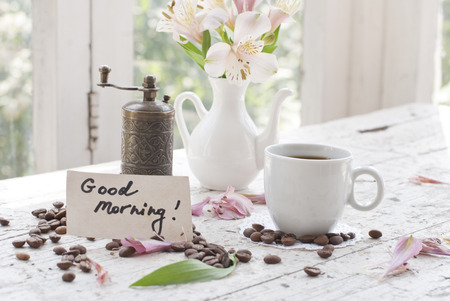 good mood: Pink Astromeria flowers in a white jar vase with good morning note and coffee beans Stock Photo