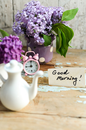good life: Two tone Lilac flowers in a ceramic pots white and purple, with pink vintage tiny alarm clock and a Good Morning note on a shabby wooden surface Stock Photo