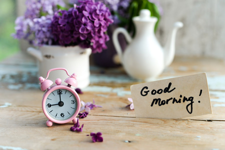 Two tone Lilac flowers in a ceramic pots white and purple, with pink vintage tiny alarm clock and a Good Morning note on a shabby wooden surface photo