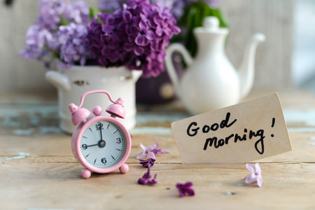 Two tone Lilac flowers in a ceramic pots white and purple, with pink vintage tiny alarm clock and a Good Morning note on a shabby wooden surface Stock Photo