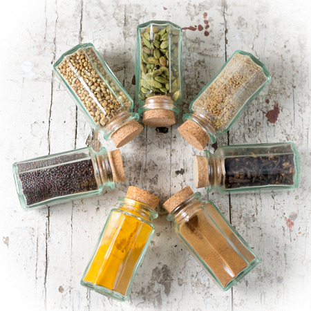 indian mustard: seven in a row transparent jars with cork closure filled with indian spices