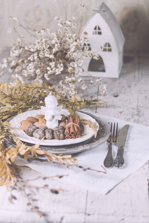Two tone plates white and grey in a vintage style, served for Christmas dinner with vintage cutlery and white napkin on a shabby white table with spices and other decorations. Stock Photo
