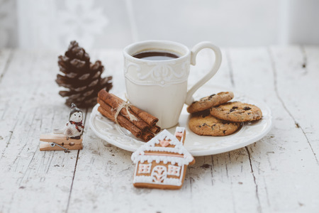 Shabby chic style coffee cup and plate with gingerbread house cookie, cinnamon sticks and other decorations for Christmas mood photo