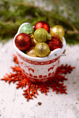 Porcelain bucket with red deer ornament full of colorful baubles for Christmas and New Year decoration with greeting card photo